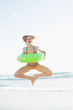 Cute woman holding a rubber ring while jumping on the beach