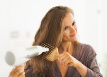 Happy Woman Brushing And Blow Drying Hair In Bathroom