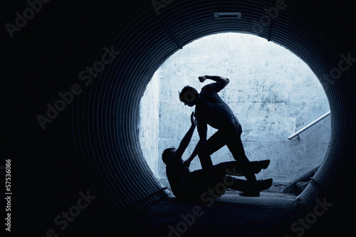 Young man being mugged in a dark tunnel Fototapete