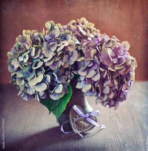 fioletowe-kwiaty-hortensji-obok-drewnianej-dekoracji-w-ksztalcie-serca-na-stole