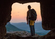 Silhouette of man with backpack in cave. Crimea.