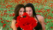 Two women smelling a poppy bouquet