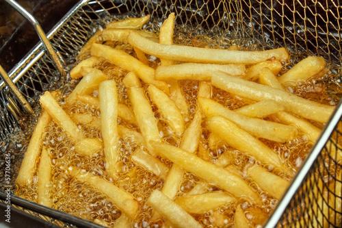 Fototapeta French fries in a deep fryer closeup