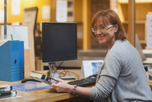 Smiling Female Librarian Holding A Book Standing Behind The Desk