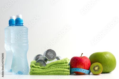 Obraz Hantle fitness z owocami i wodą na białym tle. - fototapety do salonu