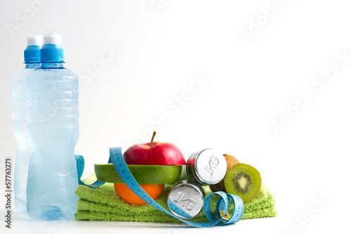Fototapeta premium Hantle fitness z owocami i wodą na białym tle.