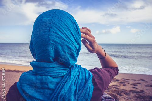Fototapeta  Rear view of woman with headscarf looking at the sea
