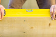 Worker Holding Spirit Level On Wood Outdoors