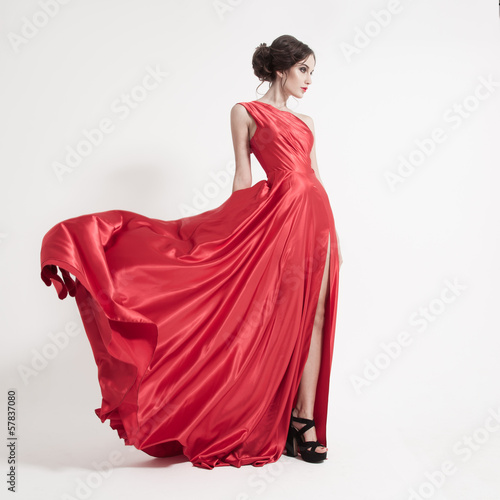 Fotografia, Obraz  Young beauty woman in fluttering red dress. White background.