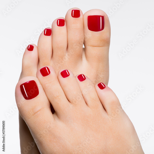 Montage in der Fensternische Pediküre Beautiful female feet with red pedicure