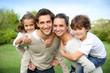 Leinwandbild Motiv Parents giving piggyback ride to children