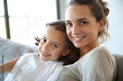 Fotografía  Mom with little girl reading book in sofa