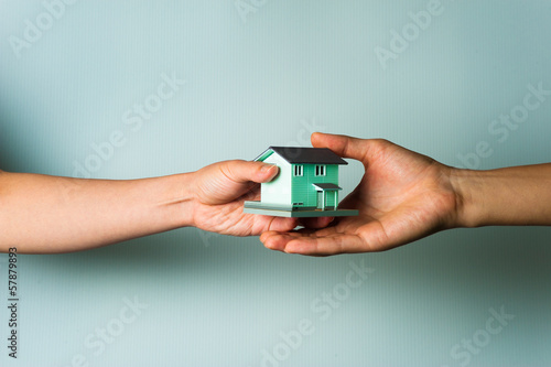 Photo ミニチュアの家を手に持っている人