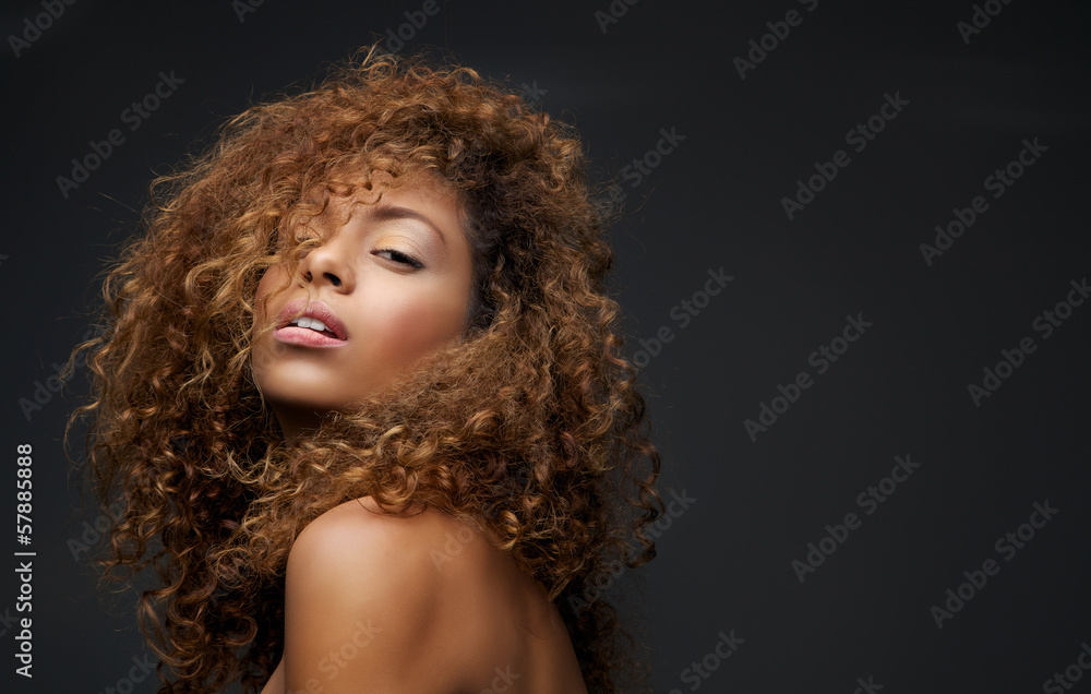 Fototapeta Portrait of a beautiful female fashion model with curly hair