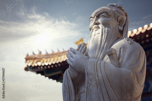 Close-up of stone statue of Confucius, pagoda roof in the background Canvas Print