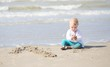 One year old baby girl plays on the beach
