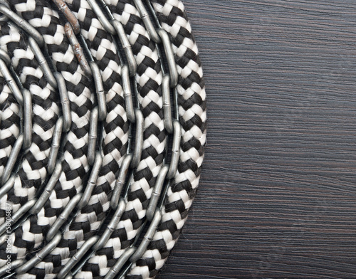 Metal chain and ship rope on dark wooden background