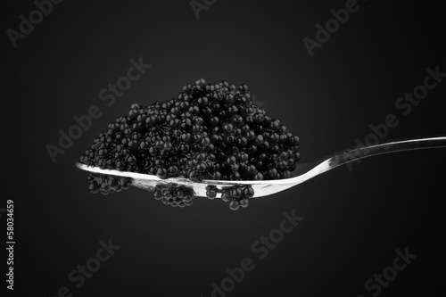 Black caviar in metal teaspoon. Macro photo