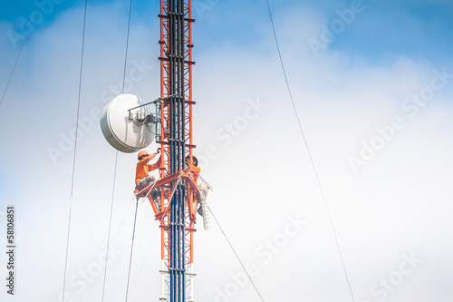 Photo  Tower climber and working on cellular tower system.