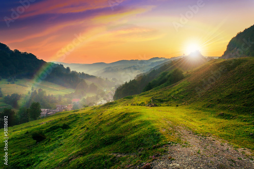 Tuinposter Landschappen hillside near the village in morning mist