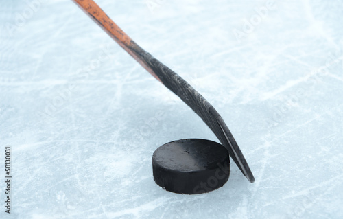ice hockey stick and puck on ice Poster