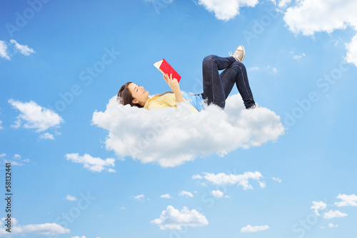 Fotografía Relaxed female reading a novel and lying on clouds