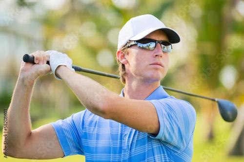 Deurstickers Golf Young man swinging golf club