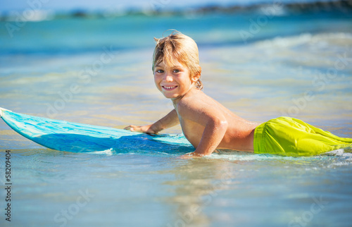 Fotografie, Obraz  happy young boy in the ocean on surfboard