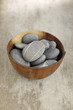 zen stones in bowl on old wood background