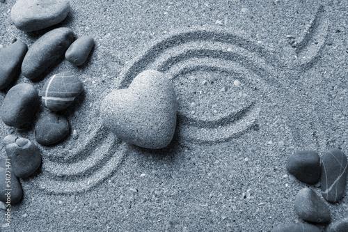 Foto op Plexiglas Stenen in het Zand Grey zen stone in shape of heart, on sand background