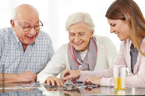 Glückliches Paar Senioren spielt Puzzle плакат