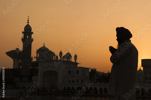 Fotografie, Obraz  Silhouette of praying sikh man at golden temple of Amritsar, Ind