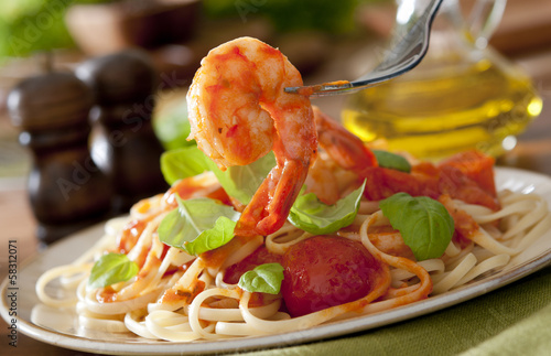 Poster Coquillage Closeup of shrimp with pasta, tomato sauce and basil.