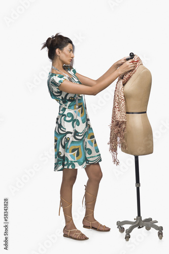 Fotografie, Obraz  Female fashion designer trying a dress on a mannequin