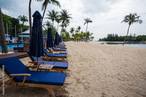 Deck chairs on the beach of Sentosa Island in Singapore. Poster