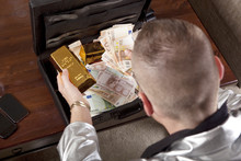 Man With Suitcase Full Of Money And Gold