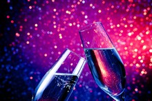Champagne Flutes With Gold Bubbles On Blue Tint Light Bokeh