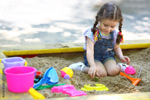 Fotografie, Obraz  Little girl sitting in sandbox and playing with molds