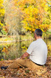 canvas print picture - Man sitting in autumn leaves by the lake