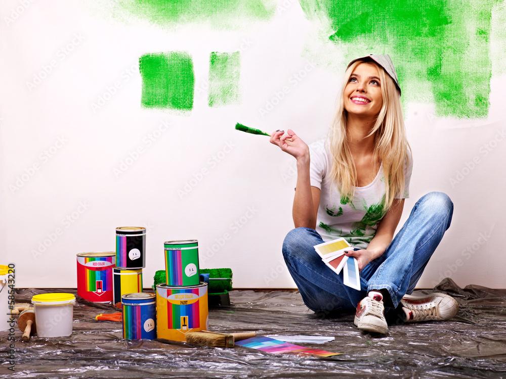 Fototapeta Woman paint wall at home.