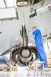 Engineer working under wing of passenger jet in hangar