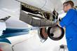 Engineer working on passenger jet in hangar