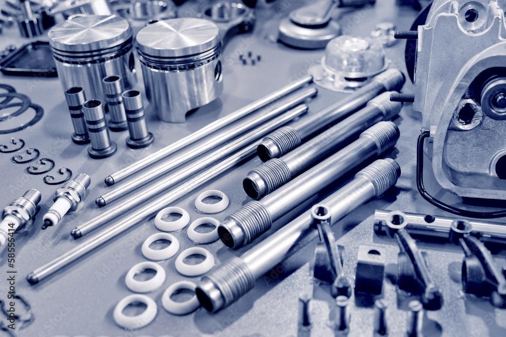 Leinwandbild Motiv - Steve Mann : blue toned precision auto engine parts laid out in a workshop