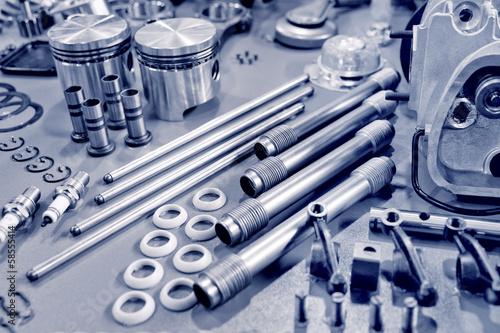 Fotografía  blue toned precision auto engine parts laid out in a workshop