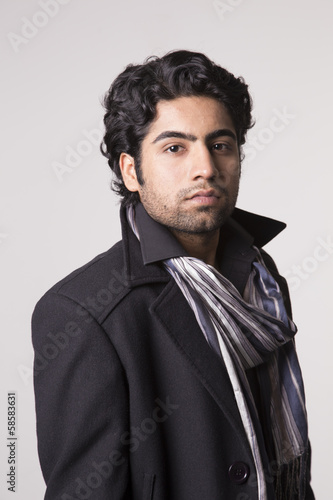 Fotografie, Obraz  Young Indian man in a scarf and overcoat