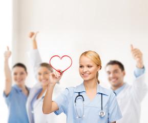 Fototapeta samoprzylepna smiling doctor or nurse drawing red heart
