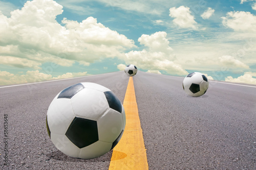 Soccer ball on the road. - 58653648