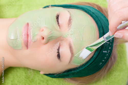 Fotografie, Obraz  Beauty salon. Cosmetician applying facial mask at woman face.