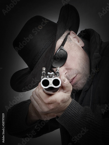 Angry gangster with shotgun aiming at you. Gun control concept.