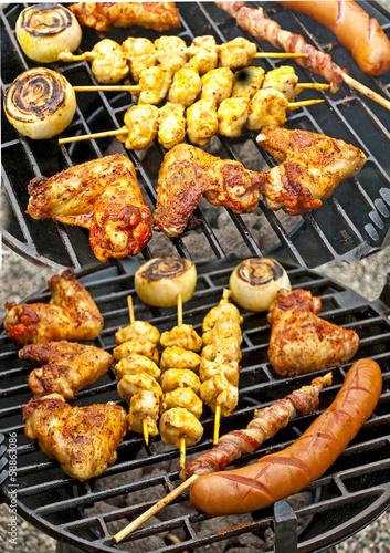 Grill mit Hühnchenflügel, Hühnchenspieß, Bratwurst, Zwiebel und Poster